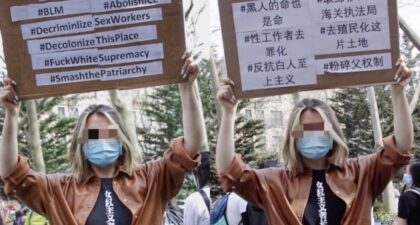 """A Chinese international student holding a bilingual sign in support the Black Lives Matter movement, sex workers' struggles, decolonization, and abolitionist projects. The Chinese slogan on her shirt translates to """"this is what a feminist looks like."""""""